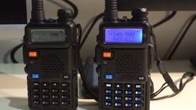 Two black handled portable walkie- talkie radio transmitter working and flashing stock video