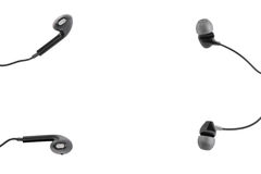 Two black headphones lie on a white isolated background. Horizontal frame Royalty Free Stock Photo