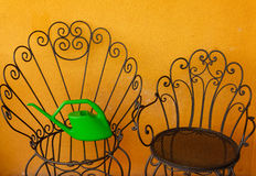 Two black iron chairs and a green watering-can  laid  on the big Royalty Free Stock Photography
