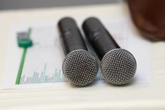 Two black karaoke microphones stand on a white table. With song list royalty free stock image
