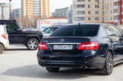 Two black Mercedes Benz E-class  rear view and G-class Gelandewagen Brabus on background in excellent condition in a parking space stock photo