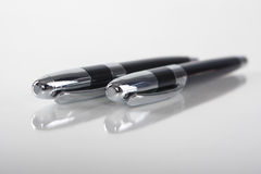 Two Black Metal Pens Isolated On White Reflective Background Royalty Free Stock Photos