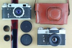 Two black old-school vintage photo cameras, brown leather case holder, films and lids. Flat lay, top view. Directly above Stock Photos