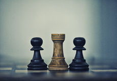 Two black pawns and a white rook Stock Images