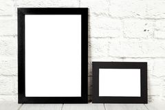 Two black photo frames on wooden table. Mockup with copy space stock photography