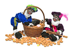 Two black piet with a basket full confetionery Royalty Free Stock Photography