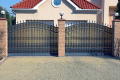 Two black metal gates with a forged pattern and brown bricks on the street near the gray pavement. Two black private metal gates with a forged pattern and brown royalty free stock photography