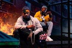 Two black rappers in caps sitting by the fire