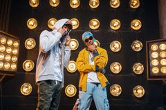 Two black rappers in caps on stage with spotlights