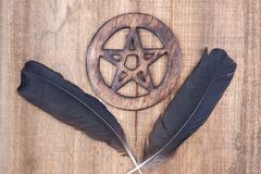 Two Black Raven feathers and Wooden encircled Pentagram symbol on wood. Five elements: Earth, Water, Air, Fire, Spirit. Two Black Raven feathers and Wooden royalty free stock photo
