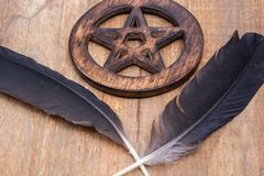 Two Black Raven feathers and Wooden encircled Pentagram symbol on wood. Five elements: Earth, Water, Air, Fire, Spirit. Two Black Raven feathers and Wooden stock photography