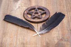 Two Black Raven feathers and Wooden encircled Pentagram symbol on wood. Five elements: Earth, Water, Air, Fire, Spirit. Two Black Raven feathers and Wooden stock image