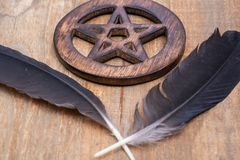 Two Black Raven feathers and Wooden encircled Pentagram symbol on wood. Five elements: Earth, Water, Air, Fire, Spirit. royalty free stock photo
