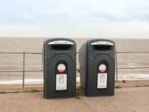 Two black recycling bins on the sea front beach for glass royalty free stock image