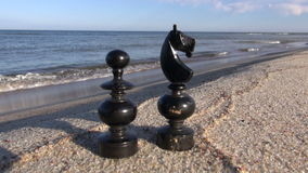 Two black retro chess pieces on  sea beach sand. Two black retro chess pieces on summer sea resort beach sand stock video footage