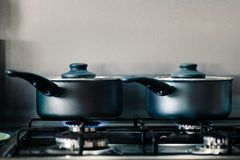 Two black shiny cooking pots on a gas hob steaming as they cook food inside royalty free stock photos