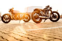 Two black and silver vintage custom motorcycles cafe racers. Two vintage custom motorbike caferacers motorcycle looking in opposite directions on empty rooftop Royalty Free Stock Image