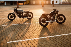 Two black and silver vintage custom motorcycles caferacers royalty free stock photos