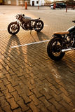 Two black and silver vintage custom motorcycles caferacers stock photos