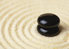 Two black stones put in a pile on sand Royalty Free Stock Photo