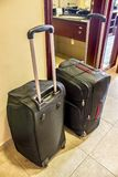 Two black suitcases with long handles in the hotel Stock Images