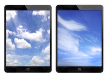 Two black tablet and blue sky background. Royalty Free Stock Photos