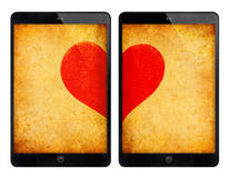 Two black tablet with red heart on grunge wall. stock images