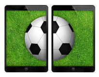 Two black tablet with soccer ball on green wall. royalty free stock photo