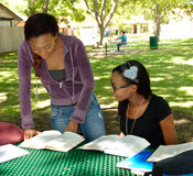 Two black teens study their books at the park. The older girls is standing and consulting a book Stock Images