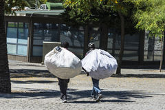 Two black vendors carrying goods in Barcelona. Barcelona, Spain - June 21, 2016: Two black sellers carrying goods within a sac known as manteros in the center of Royalty Free Stock Photos