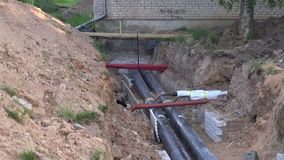Two black water heating pipes in a ditch stock footage