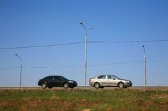 Two black and white cars and three street lamps Royalty Free Stock Photo