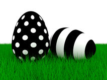 Two black an white Easter eggs lying on green grass Royalty Free Stock Images