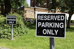 Two black and white  reserved parking only signs located at Warr. Ington Town Hall Bank Park Warrington Cheshire May 2018 Stock Photo