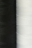 Two black and white spools of thread close-up Stock Images