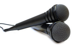 Two black wired karaoke microphones. Royalty Free Stock Photos