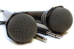 Two black wired karaoke microphones. Royalty Free Stock Photo
