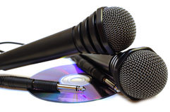Two black wired karaoke microphones and CD. Royalty Free Stock Image