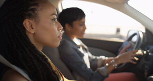 Two black women friends sitting in car talking to each other. On road trip stock image