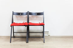 Two black wooden chairs with soft pillows are near wall Royalty Free Stock Photo