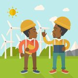 Two black workers talking infront of windmills Stock Photography