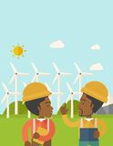 Two black workers talking infront of windmills Royalty Free Stock Photos
