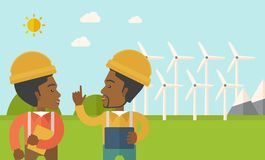 Two black workers talking infront of windmills Royalty Free Stock Photography