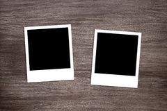 Two blackened instant photo print templates on wooden background Royalty Free Stock Image