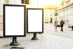 Two blank advertising billboards on the city street. With pedestriants and sun glow Stock Photography