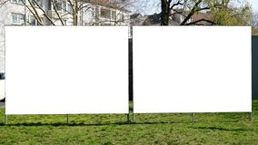 Two blank billboards side by side. Two blank empty billboards side by side on urban roadside greenery royalty free stock images