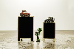 Two blank black boards with car on top on world map with palm tree Royalty Free Stock Photo