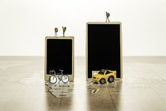 Two blank black boards with tiny human model with car and bicycle on world map Royalty Free Stock Photos
