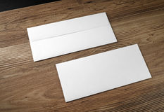 Two blank envelopes. Blank envelopes on wooden table background. Front and back side stock photo