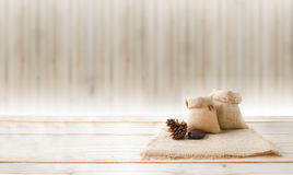 Two of blank hemp sack bag and pine cones on wood table top floo Royalty Free Stock Image